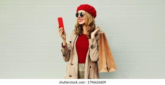 Herbstporträt einer lächelnden Frau mit Smartphone und Einkaufstasche mit einem Mantel, rote, französische Bette auf grauem Hintergrund