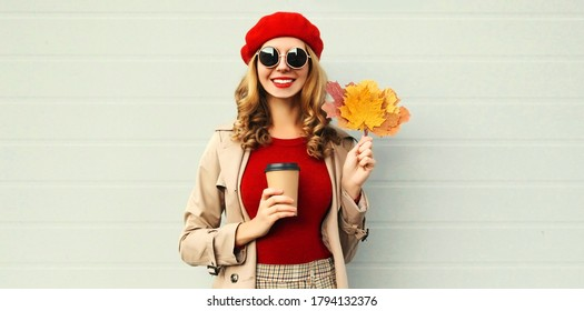 Autumn portrait of smiling young woman with yellow maple leaves and cup of coffee wearing red french beret over gray background