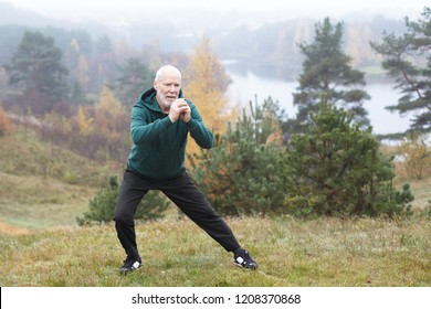 Autumn portrait of sporty healthy mature male in hoodie and running shoes exercising outdoors, practicing side lunges. Elderly bearded man in sportswear warming up before morning run in park