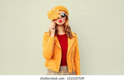 Autumn portrait woman holding in her hands yellow maple leaves covering her eye, girl blowing red lips sending sweet air kiss over gray wall background