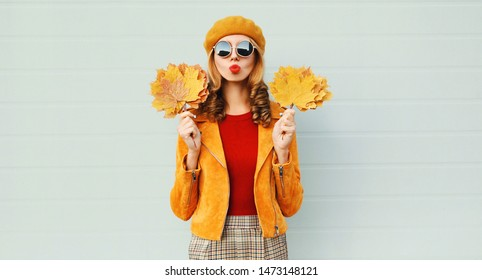 Autumn portrait woman holding yellow maple leaves blowing red lips sending sweet air kiss in french beret posing over gray wall background
