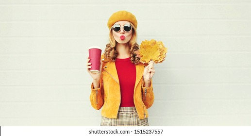 Autumn portrait woman with yellow maple leaves, coffee cup blowing red lips sending sweet air kiss over gray wall background