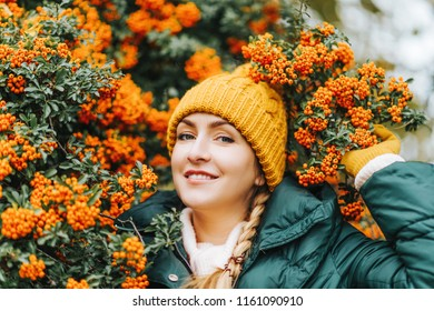 Autumn portrait of young beautiful woman wearing green jacket and set of yellow hat and gloves, posing next to bright orange scarlet firethorn berries (Pyracantha coccinea)
