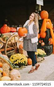 Autumn portrait of young happy woman on farm market