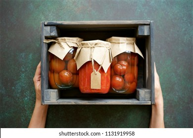 Autumn preserves of tomatoes and vegetable puree in glass jars placed in wooden box. Homemade autumn canning products