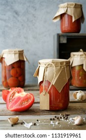 Autumn preserves of tomatoes and vegetable puree in glass jars. Homemade autumn canning products