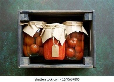 Autumn preserves of tomatoes or vegetable puree in glass jars placed in wooden box. Homemade autumn canning products