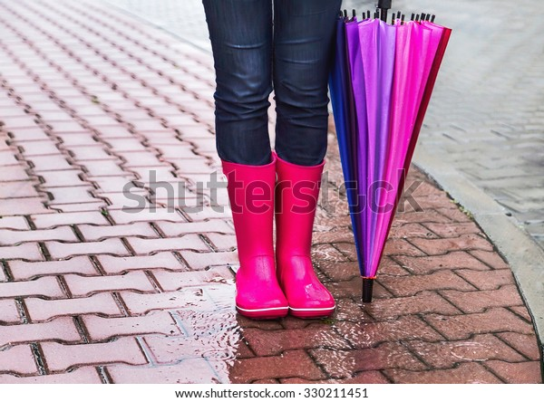Autumn. Protection in the rain. Woman (girl) wearing pink rubber boots and has colorful  umbrella. Street, city. Raindrops. Copy space. Place for message. Concept about activity, leisure, travel.