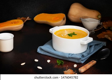 Autumn Pumpkin Cream Soup on a dark table and black background, served with cream, pumpkin seeds and mint. Cut pumpkin, autumn leaves, spoon, white plate. Close-up