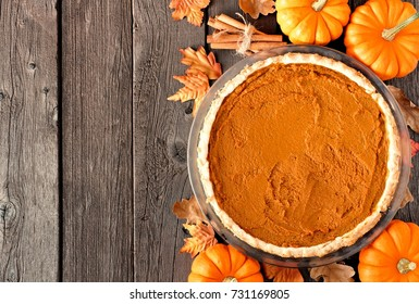 Autumn pumpkin pie, overhead table scene on a rustic wood background