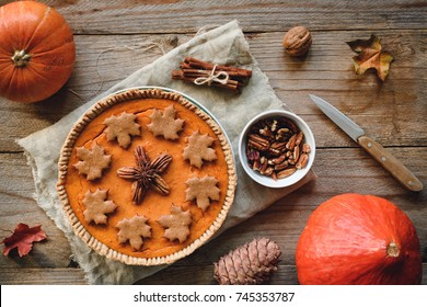 Autumn pumpkin pie with pecan nuts and gingerbread spice cookies on wooden table. Table top view