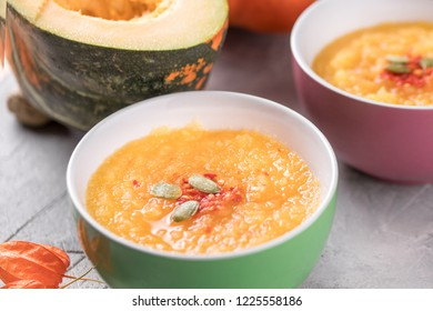 Autumn pumpkin puree soup in ceramic cups on a gray textural background. Close-up.