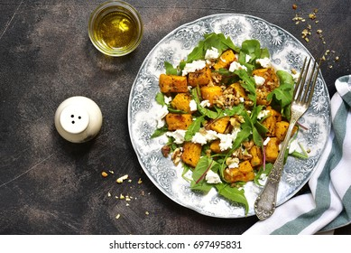 Autumn pumpkin salad with feta,arugula,chard and walnut on a vintage plate over dark slate,stone or concrete background.Top view.