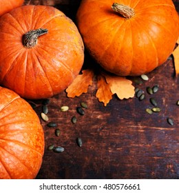 Autumn Pumpkin Thanksgiving Background - orange pumpkins over wooden table with copy space and autumn leaves