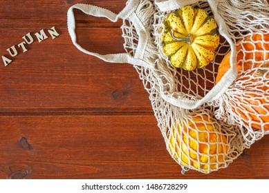 Autumn pumpkin Thanksgiving background with autumn word, in zero waste reusable bag over wooden table, flat lay, top view