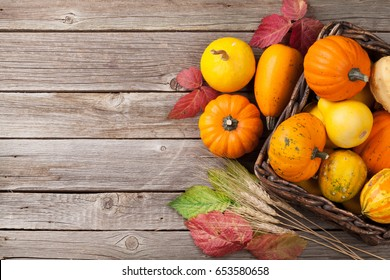 Autumn pumpkins in box on wooden table. Top view with copy space