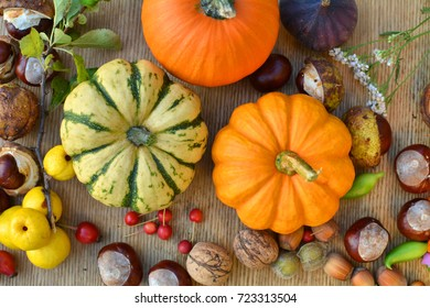 Autumn pumpkins, nuts and fruits on wooden background