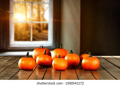 Autumn pumpkins on table and blurred background of autumn window.