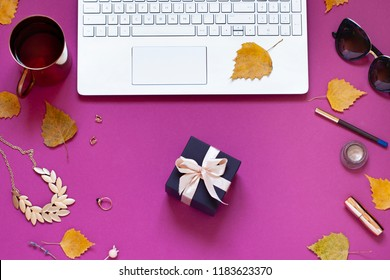 Autumn purple fashion business flat lay with yellow fall leaves and a gift. Top view beauty composition