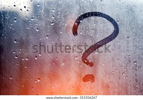 Autumn rain, the inscription on the sweaty glass - question mark