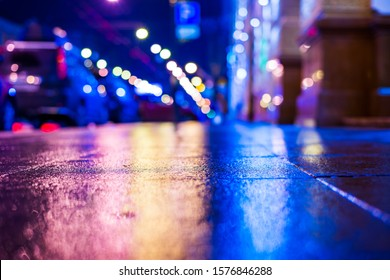 Autumn rainy night in the city. Empty street. Parked cars. Light from shop windows is reflected on the sidewalk. Close up view from the level of the pavement. Blue tones.