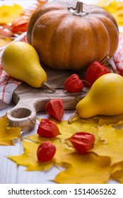 Autumn ripe pumpkins with yellow leaves and physals on a wooden board. Halloween concept.