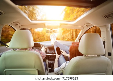 Autumn road and two lovers on trip in car