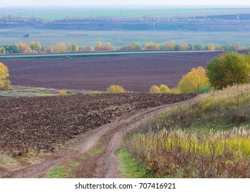 Autumn, the road is unpaved, freshly plowed field, a hill covered with beautiful autumn trees