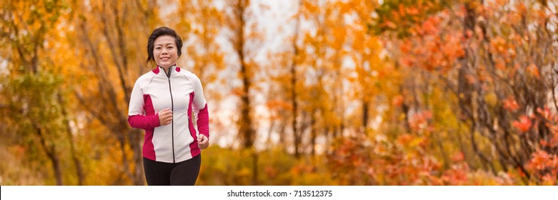 Autumn running middle age Asian woman jogging in park banner panorama. Active lifestyle mature lady in her 50s living a healthy life.