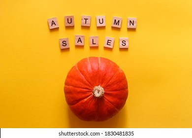 Autumn sales concept. Pumpkin and inscription AUTUMN SALES made from wooden letters on a bright yellow background. Shopping concept, seasonal sales.