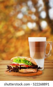 Autumn sandwich with vegetables and coffee on cutting board on wooden table.