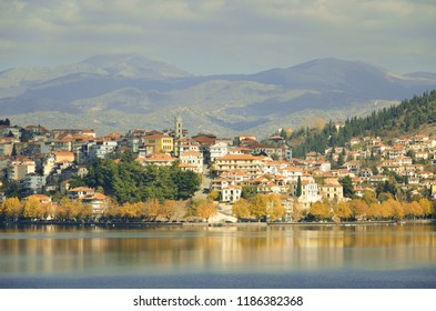 Autumn scene with amphitheatrical houses and trees with yellow fall leaves at the waterfront of lake Kastoria