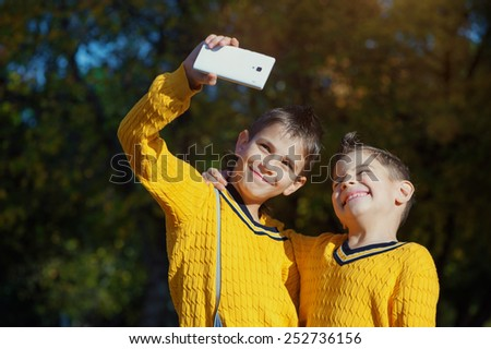 Autumn scene of Happy hugging young brothers taking selfie with a smartphone in the park