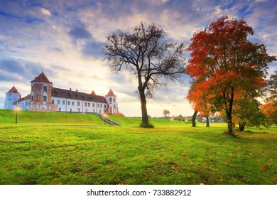 Autumn scene. Mir castle complex in autumn evening. Beautiful autumn park with maple.