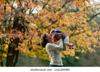 Autumn scene of mother kissing young baby girl outdoors with colorful trees in park.