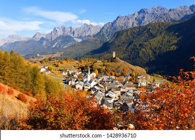 Autumn scene of a ruined fortress on a hilltop under rocky alpine mountains & village houses sprawling on the hillside of colorful trees in Engadin Valley on a sunny day in Ardez, Grisons, Switzerland
