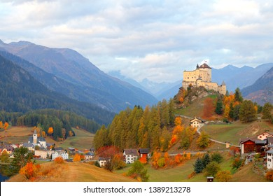 Autumn scene of Tarasp Castle perched on a hilltop with colorful trees and village houses in the valley embraced by alpine mountains on a sunny cloudy day in Scuol, Grisons (Graubunden), Switzerland