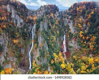 Autumn scenery of Ginga and Ryusei Waterfalls in Sounkyo Gorge, with beautiful fall colors on the rocky cliffs & majestic Kurodake mountain in background, in Daisetsuzan National Park, Hokkaido, Japan