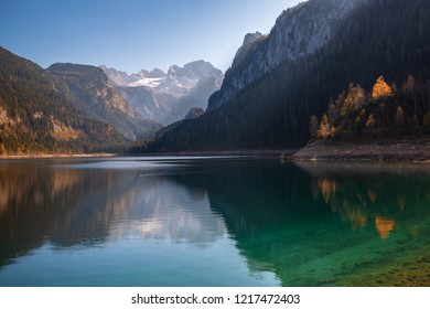 Autumn scenery of Gosausee lake with mountains reflected in the surface water and Dachstein mountain summit (World UNESCO heritage site) on background, Salzkammergut region, Upper Austria
