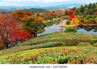 Autumn scenery from a hillside in Shugaku-in Imperial Villa (Royal Park) in Kyoto, Japan, with fiery maple trees reflected in the peaceful water of a lake and red leaves fallen on the lakeside meadows