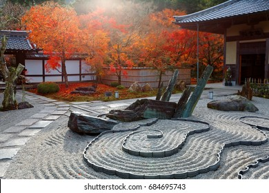 Autumn scenery of a Japanese rock garden ( zen garden, dry landscape, or karesansui ) in morning sunlight, at Honryutei in Enkouji, a Buddhist Temple famous for its fiery maple foliage in Kyoto, Japan