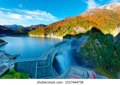 Autumn scenery of Kurobe Dam on a brisk sunny day, in Tateyama Kurobe Alpine Route, Japan, with beautiful fall foliage on lakeside mountains and an awesome view of water release into the deep gorge