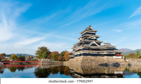 Autumn scenery of Matsumoto castle. Bright blue sky reflects on the moat. Taken at Matsumoto, Nagano Prefecture, Japan