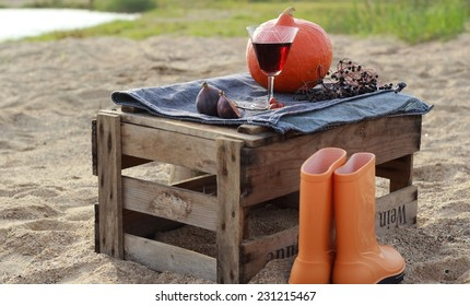 Autumn scenery with pumpkin and rain boots in the box after the wine on the beach/Autumn picnic on the beach