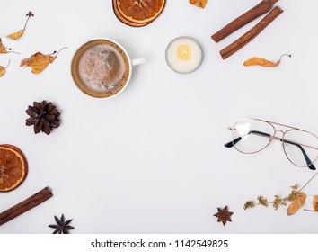 Autumn season flat lay. Cofffee, candle and dry spices and leaves on white background.
