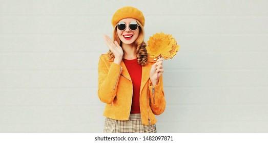 Herbstsaison! glückliche überraschte Frau mit gelben Ahornblättern auf grauem Hintergrund
