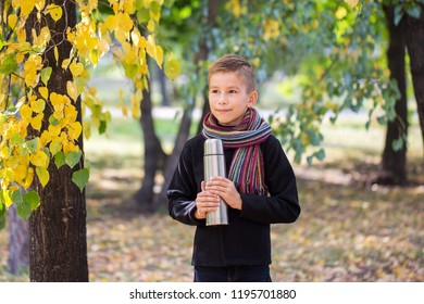 Autumn season. Walk in nature. Forest rest. Child boy is holding a metal thermos in his hands with hot tea. Picnic.