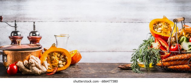 Autumn seasonal  cooking concept. Various autumn seasonal organic vegetables: pumpkin,carrot,paprika,tomatoes,ginger in basket on wooden kitchen desk tables with pot at wall background, front view.