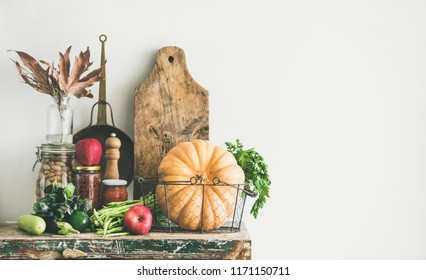 Autumn seasonal food ingredients, kitchen utensils. Vegetables, pumpkin, apples, canned food, fallen leaves over rustic wooden chest of cupboard, copy space. Thanksgiving dinner preparation