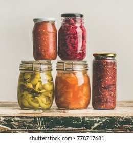 Autumn seasonal pickled or fermented colorful vegetables in glass jars over vintage kitchen drawer, white wall background, copy space, square crop. Fall home food preserving or canning